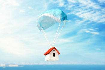 A Toy House Flies On A Parachute From A Medical Mask. The Concept Of A Protected House From Viruses