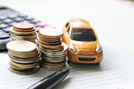 voiture miniature, pile, calculatrice illustrant le credit auto